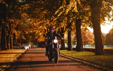 Man riding a cafe-racer motorcycle outdoors