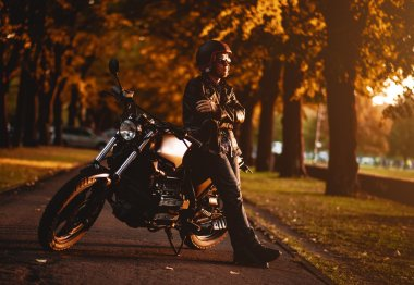 Motorcyclist with a cafe-racer motorcycle outdoors