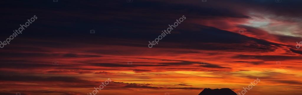 Panoramic view of a beautiful bright sunset with cloudy sky