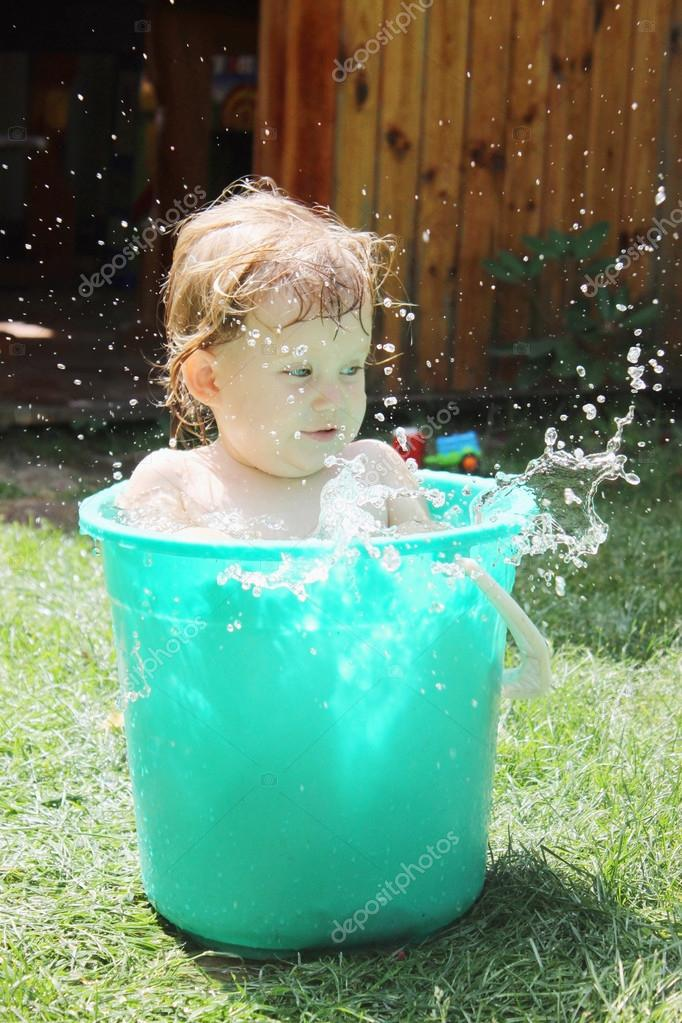 Little girl bathes in a bucket