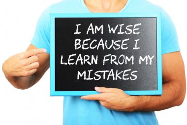 Man holding blackboard in hands and pointing the word I AM WISE