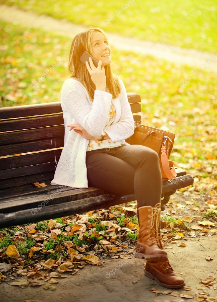 Happy young woman talking on phone in Autumn park