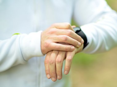 Runner on mountain trail looking at sports smart watch