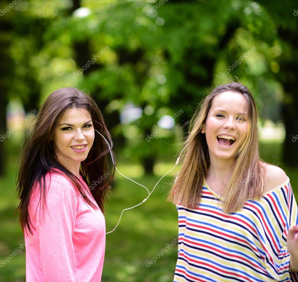 Female student girls outside in park listening to music on headp
