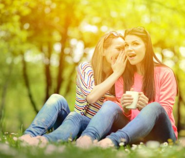 Young women drinking coffee at park and whispering secrets on be