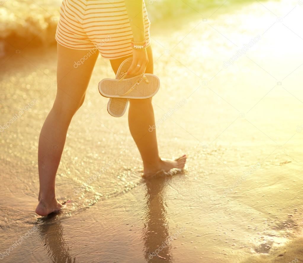 Beach travel - woman walking on sand beach leaving footprints in
