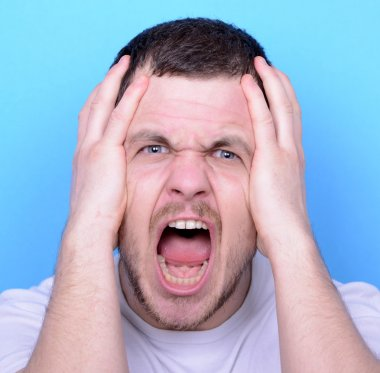 Portrait of angry man screaming and pulling hair against blue ba