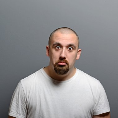 Portrait of a confused man against gray background
