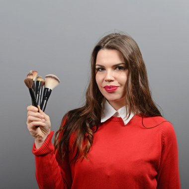 Portrait of woman holding make-up brushes against gray backgroun