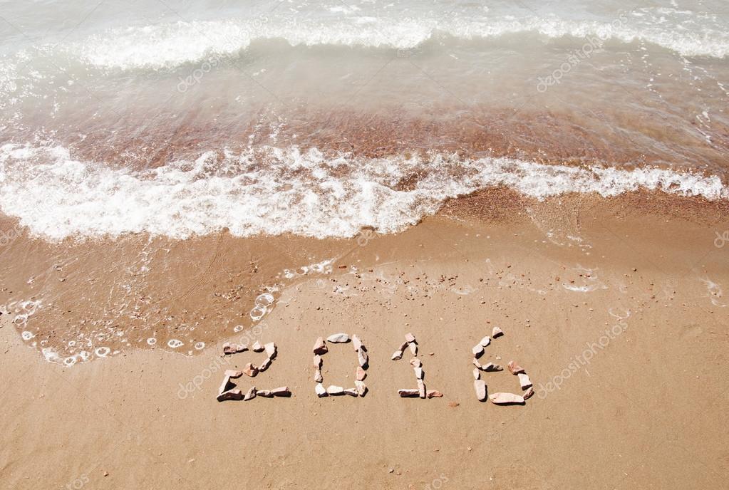 2016 written in sand on sunny beach