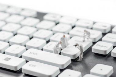 Group of miniature criminalists inspecting computer keyboard.  Cybercrime concept