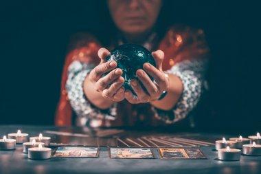 Falcı elinde mumların yanındaki masada tarot kartlarıyla. Tarot kartları kristal kürenin üzerine yayılmış. Tahmin konsepti..