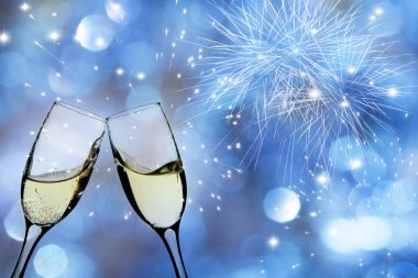 Champagne glasses against holiday lights and fireworks