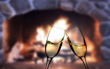 Glasses of champagne in front of warm fireplace