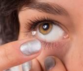Mladá žena uvedení kontaktní čočky v oku.