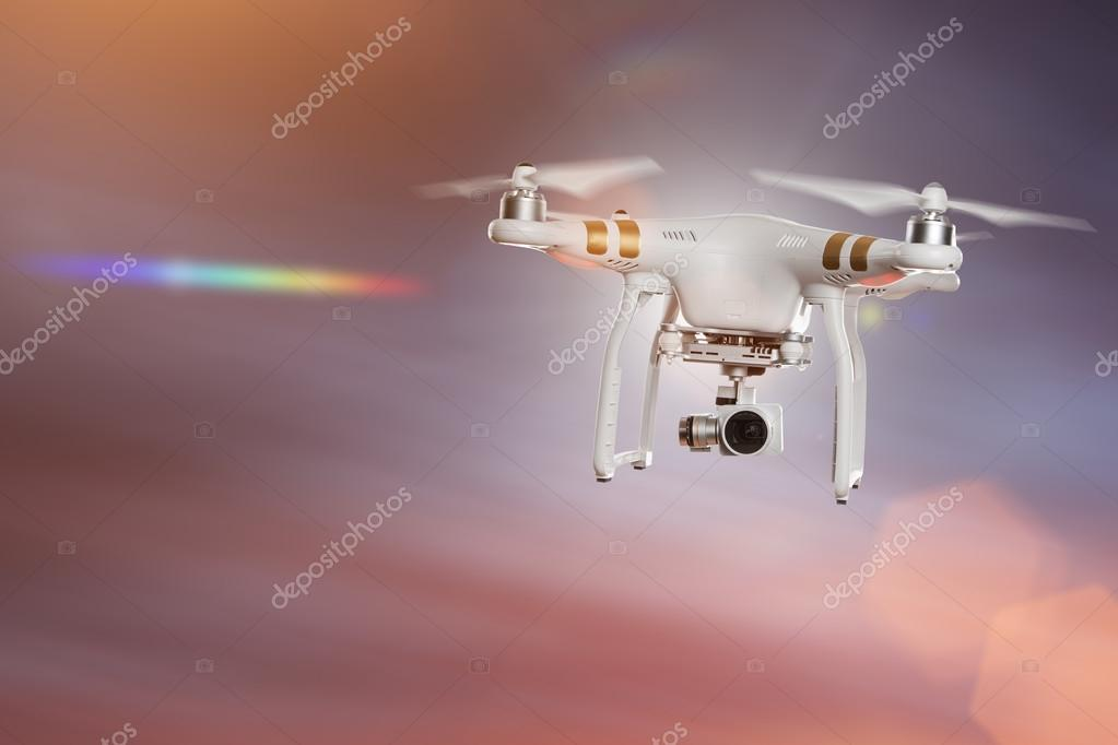 White drone quad copter with 4K digital camera flying.