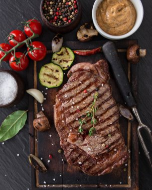 Delicious beef steak on black stone table.