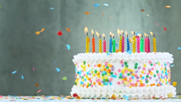 Geburtstagstorte mit brennenden bunten Kerzen auf grauem Hintergrund. Superzeitlupe.