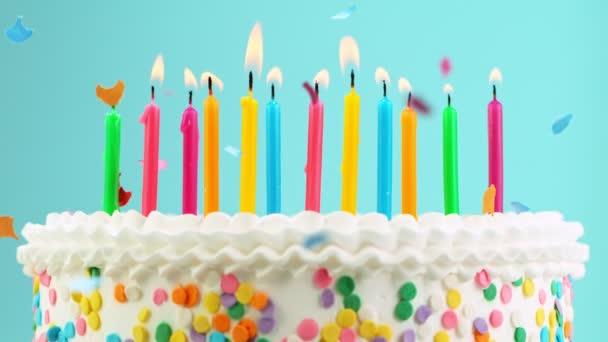 Narozeninový dort s hořící barevné svíčky na pastelově modrém pozadí. Super pomalý pohyb.