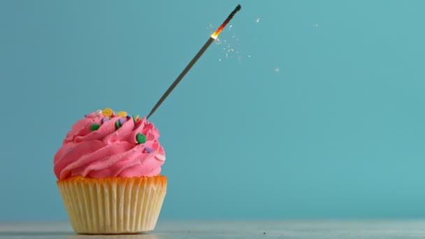 Születésnapi sütemény égő csillagszóróval pasztell kék háttérrel. Szuper Lassú Mozgások.