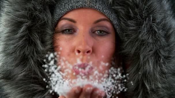Krásný portrét brunetky ženy v zimě fouká sníh z jejích rukou směrem k fotoaparátu. Super pomalý pohyb.