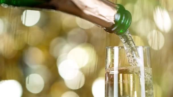 Píšťalka se šumivým šampaňským Víno nad zlatým blikajícím pozadím.