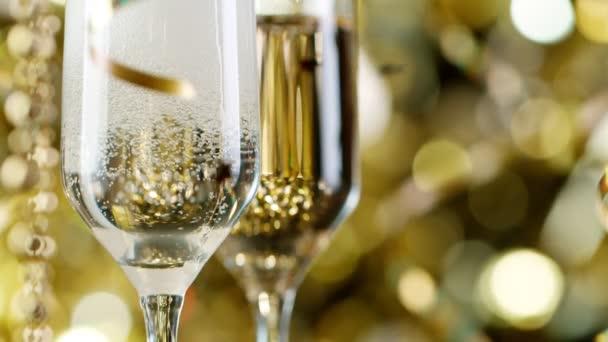 Flétny se šumivým šampaňským Víno nad zlatým blikajícím pozadím.