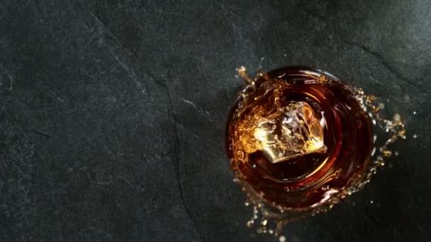 Super Slow Motion Macro Top Shot of Splashing Whiskey üvegbe jégkockákkal