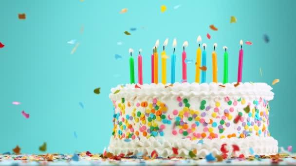 Narozeninový dort s hořící barevné svíčky na pastelově modrém pozadí.