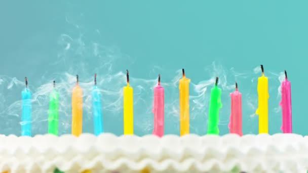 Születésnapi torta égő színes gyertyák pasztell kék háttér.