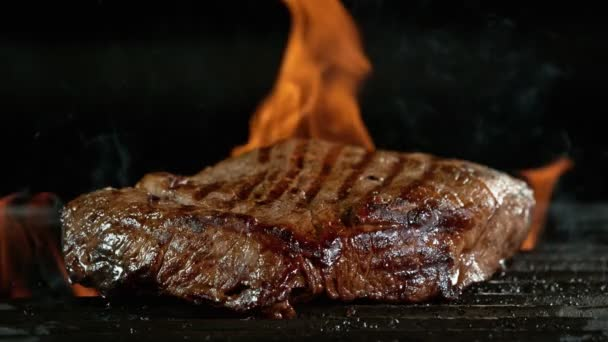 Detailní záběr chutného hovězího steaku na litinovém roštu