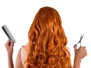 Cutting young beautiful brunette woman's hair