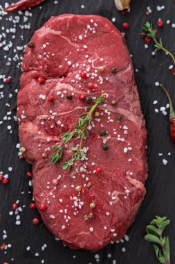 Raw beef rump steak onblack table