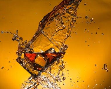 Whiskey with ice with liquid splash