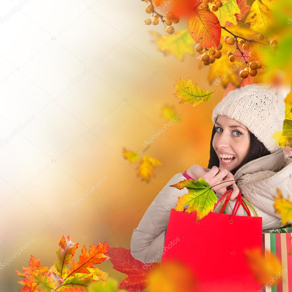 Beautiful woman holding shopping bags, buying in autumn season.