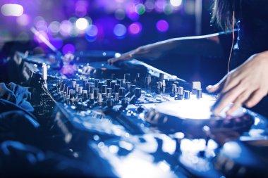 Dj mixes the track in the nightclub.