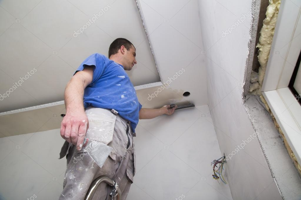 Plasterer with putty knife working on apartment wall
