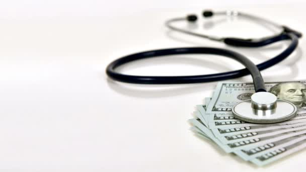 Stethoskop und Geld auf weißem Hintergrund. Zeitlupeneffekt