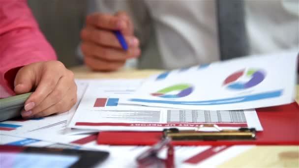 Zaměstnanci firmy zkoumá výroční zprávy na stole. Efekt zpomaleného pohybu
