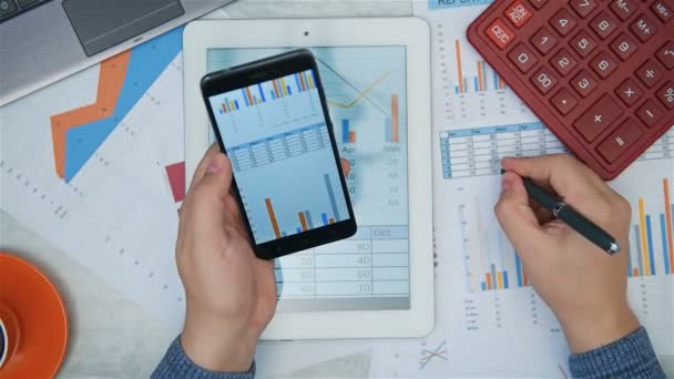 Businessman Analyzing Stock Report On Smart Phone And Digital Tablet On Office Desk. Finance And Trade Concept.