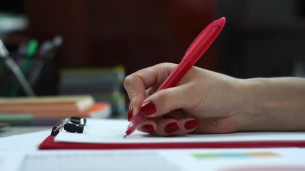 woman with red pen signs contract