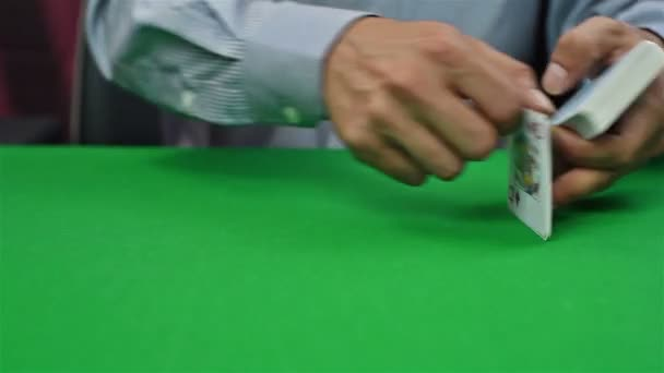 poker croupier distributes cards on green table