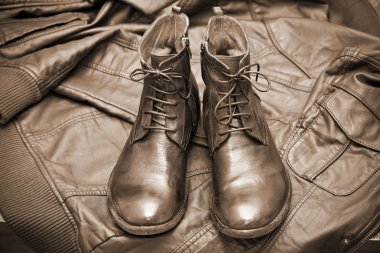 Fashionable leather boots and leather jacket. Autumn and spring season. Autumn and spring shoes. Photo toning in sepia