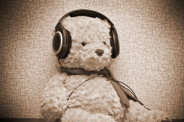 Teddy bear listening to music on headphones. Photo by sepia toned