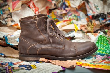 Men's leather boots crumpled sheets of colored paper. grunge style