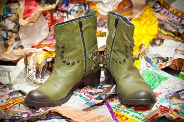 Women's green leather boots crumpled sheets of colored paper. grunge style. Autumn - spring shoes