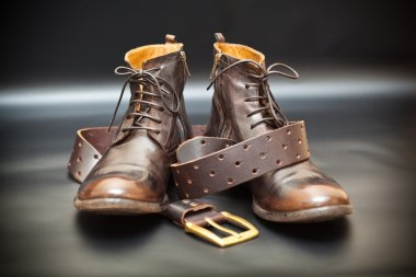 Cool men's leather shoes and a leather belt with a buckle on a dark abstract background. Autumn - spring shoes