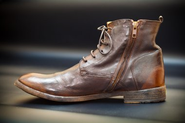 Fashionable men's leather shoes on a dark abstract background. Autumn - spring shoes. brown boots closeup