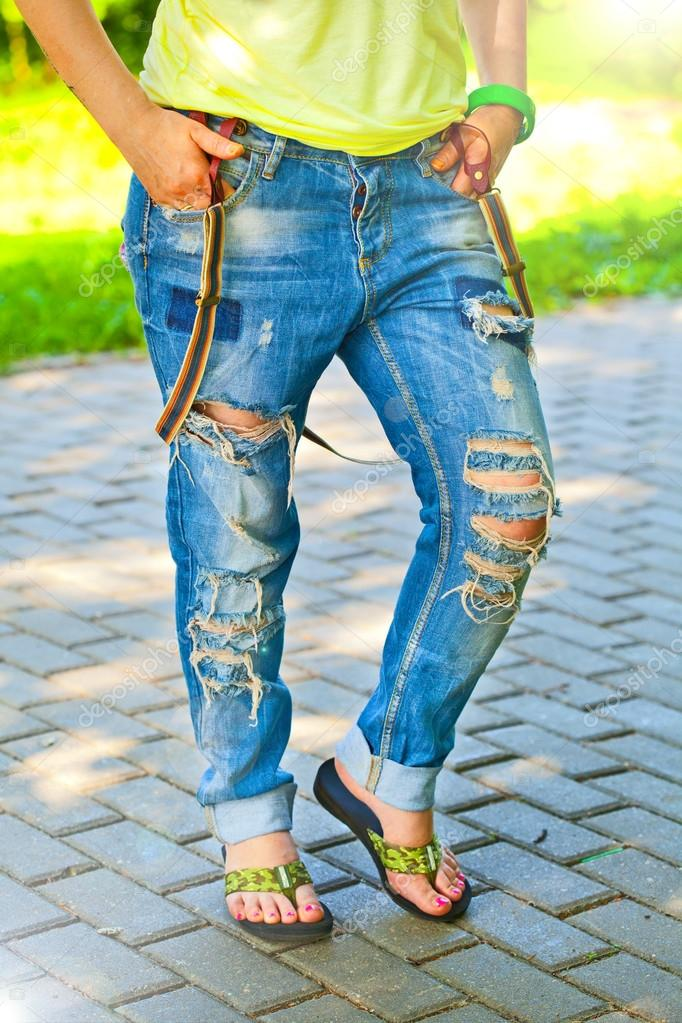 Photo girl in jeans with holes in sunny summer weather outdoors closeup