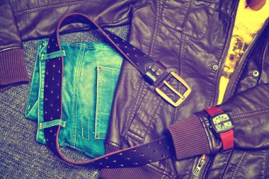 Clothing items and accessories: blue jeans with a leather belt, leather jacket, T-shirt, watches